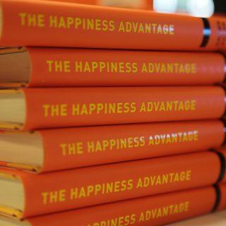 Plusieurs exemplaires du livre de Shawn Achor empilés