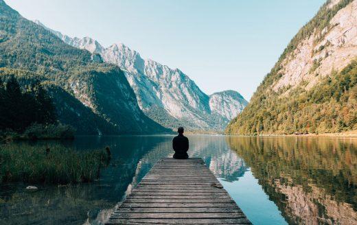 Personne assise sur un ponton au bord d'un lac à la montagne