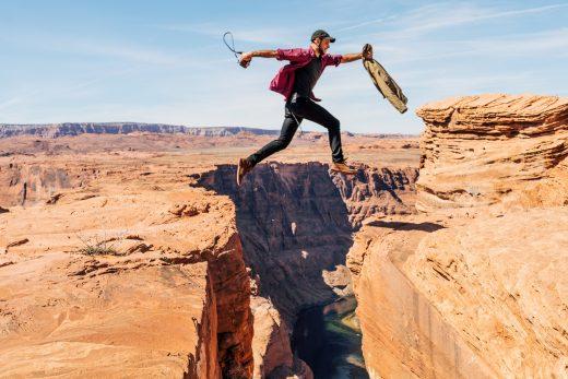 Homme qui saute au dessus d'un ravin