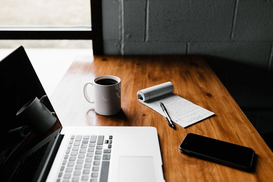 Bureau avec ordinateur portable, mug de café, calepin, stylo et smartphone