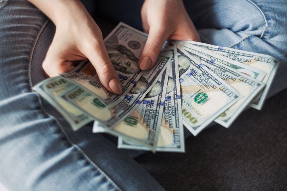 Une femme comptant des dollars américains