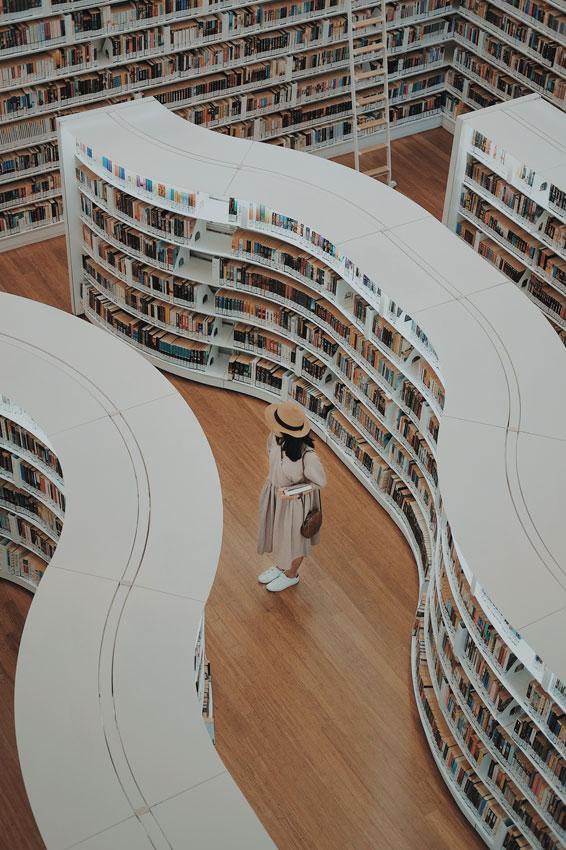 Femme dans les allées d'une bibliothèque
