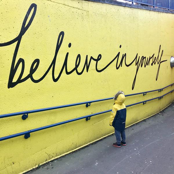 """Enfant face à un mur portant l'inscription """"believe in yourself"""""""