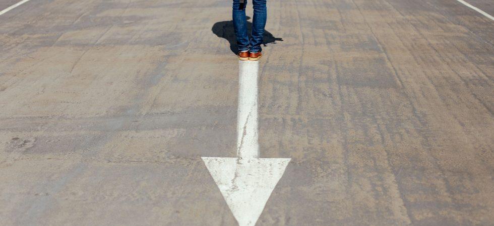 Personne debout sur une route avec une flèche allant vers l'arrière