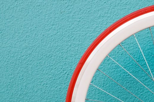 Roue de vélo rouge et blanche sur fond turquoise