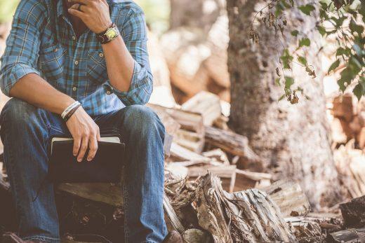 Homme assis sur du bois coupé qui réfléchit