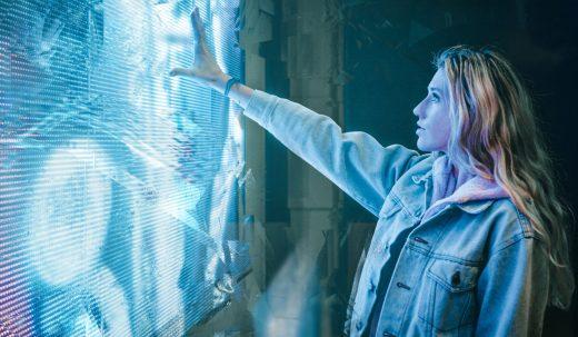 Jeune femme touchant un écran qui se décompose à son contact