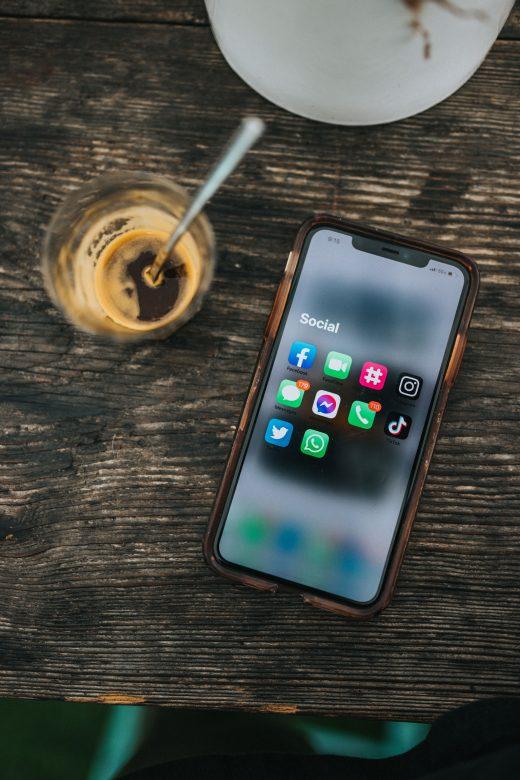 Smartphone posé sur une table en bois à côté d'un café