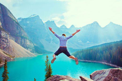 Jeune homme qui saute d'une falaise vers un lac en contrebas