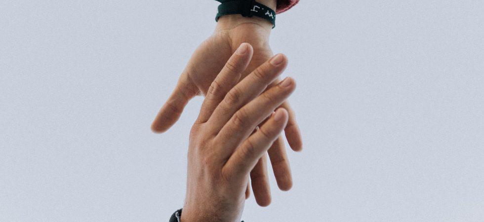 Photo d'une main sur le point d'en saisir une autre