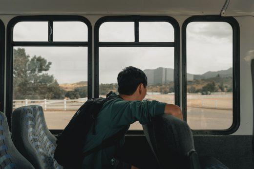 jeune homme regardant par la fenêtre d'un bus